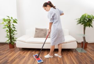 A maid cleaning the floor with a mop