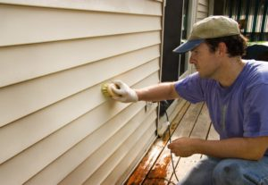 A man cleaning a vinyl siding