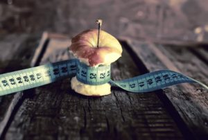 Anorexia sign with a measuring tape tied in an apple
