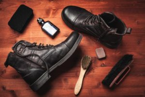 hipster boots on a table with shoe polishing materials