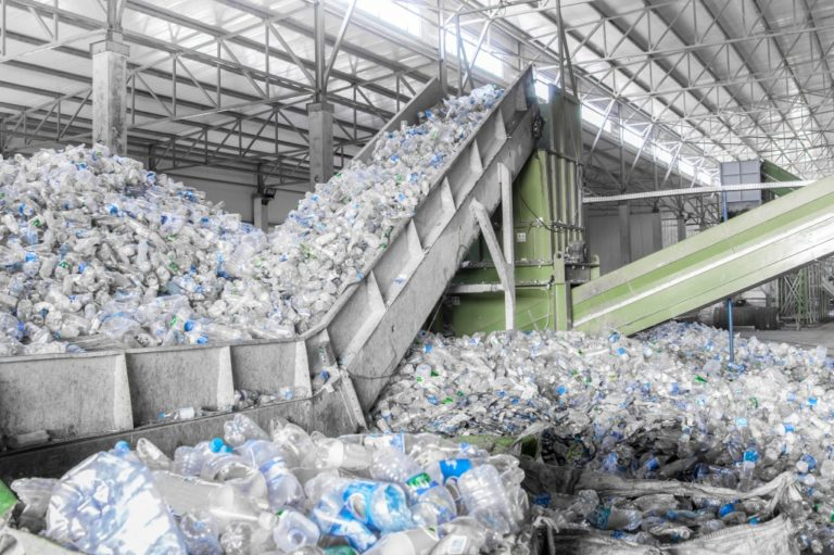 pile of plastic bottles on the process of recycling