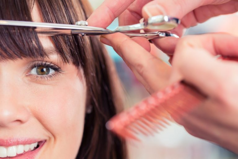 scissors cutting woman's bangs