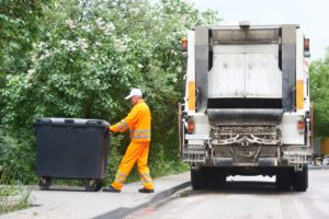 Worker collecting trash from dumpster