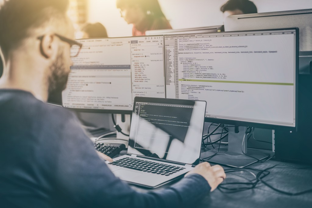 Software developer working with multiple screens