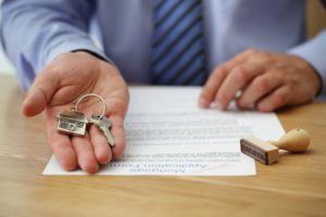 Person handing the key to a new home