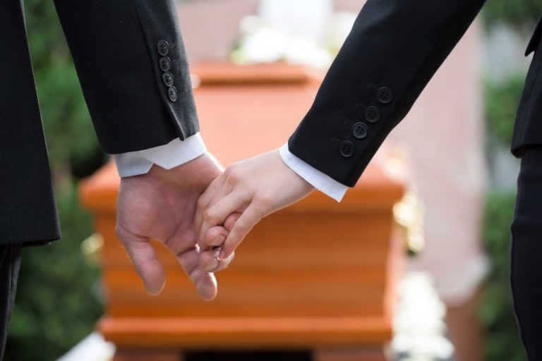 two people holding hands in a funeral