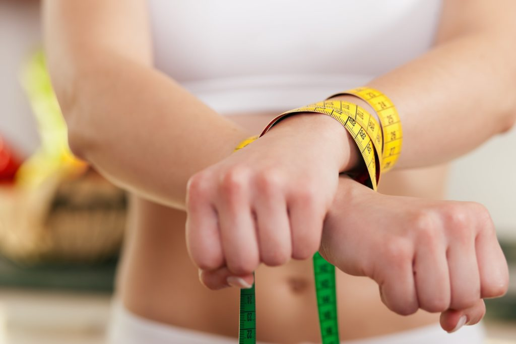 eating disorder concept, woman' hand tied with measuring tape