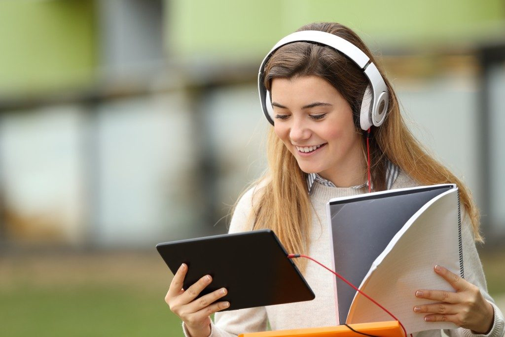 woman listening to music while taking online class