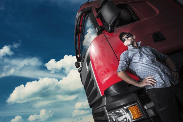 Driver posing beside a red truck