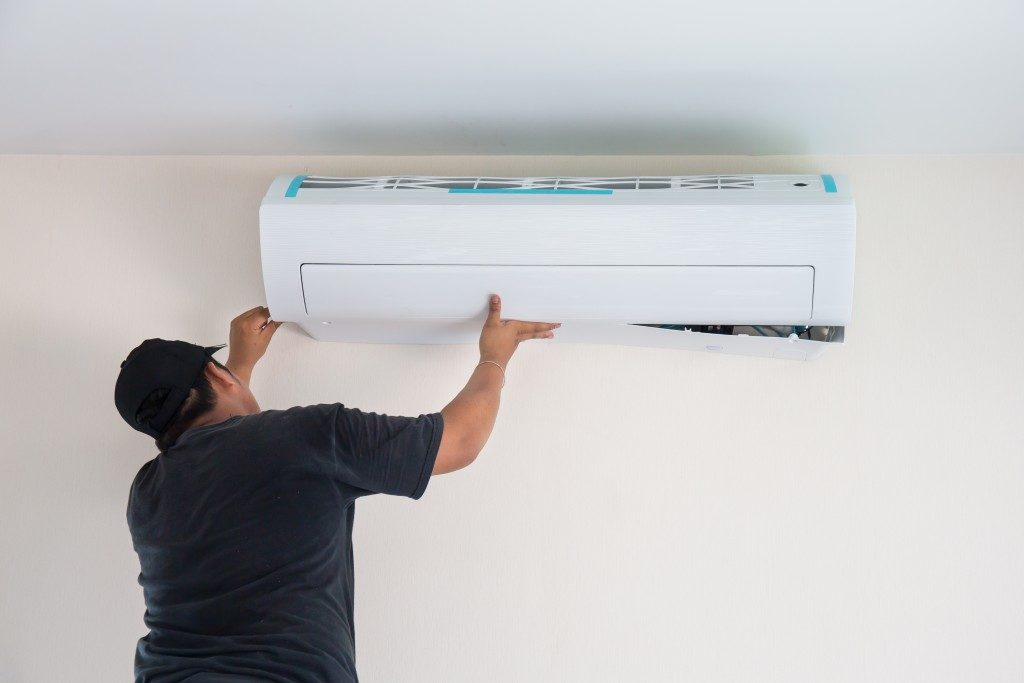 Worker installing a new air conditioning unit