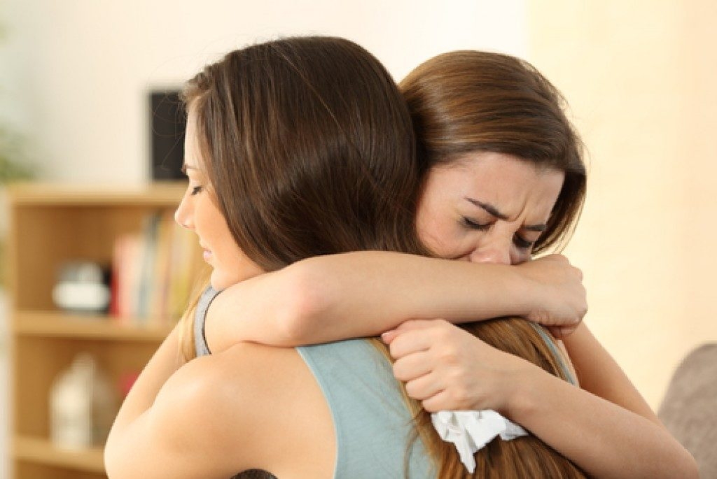woman comforting the other who is crying