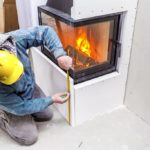 construction worker measuring fireplace