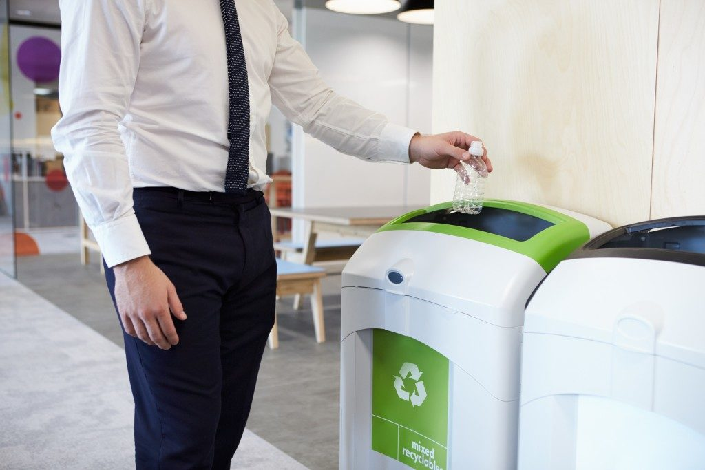 man throwing plastic bottle in recycling bin