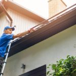 Man cleaning aluminum gutter