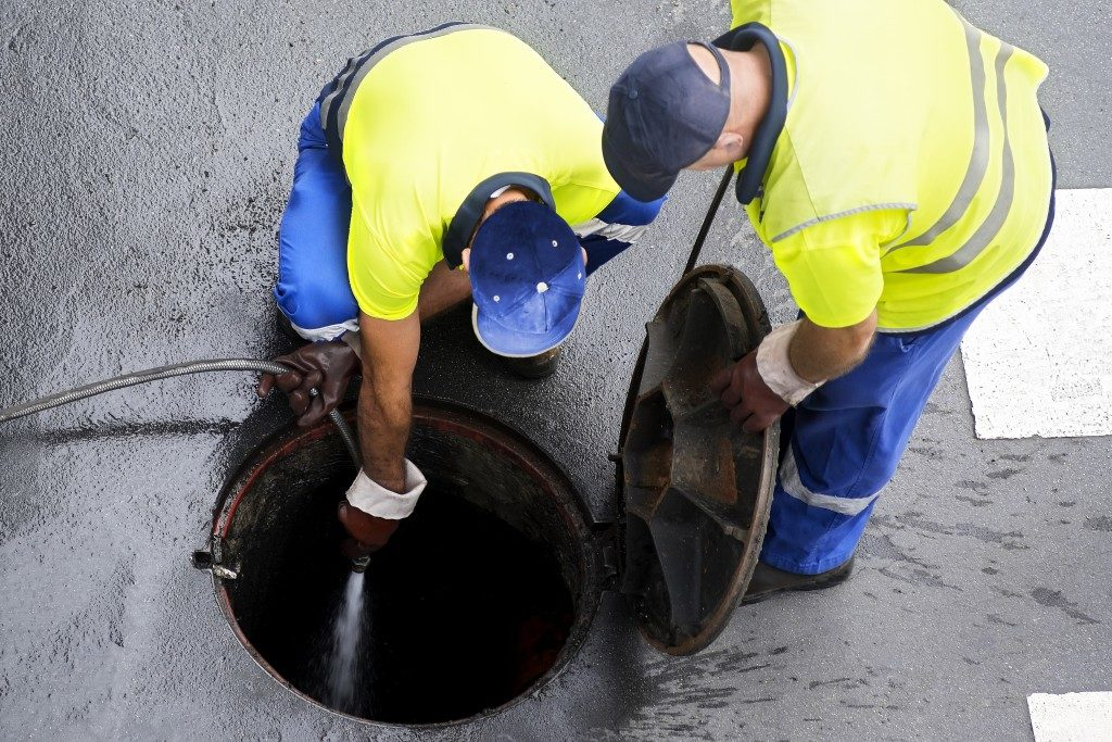 Man cleaning the sewage line