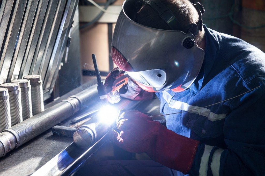 man wearing mask welding pipes