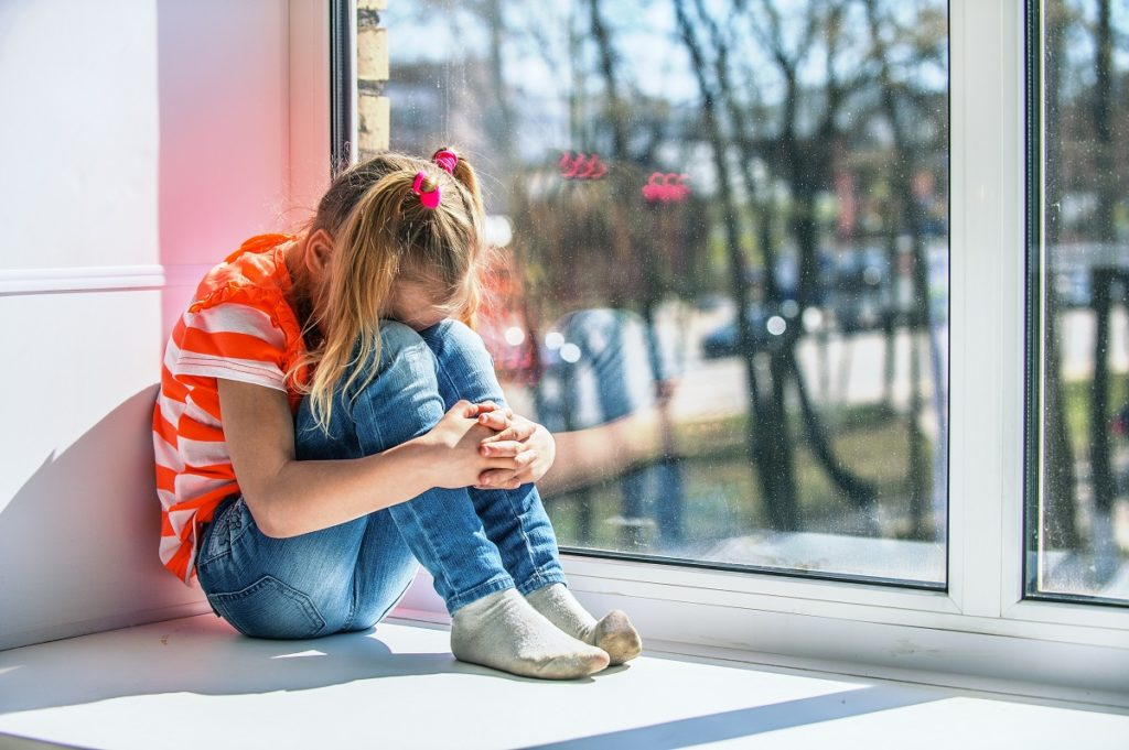 Girl crying beside the window