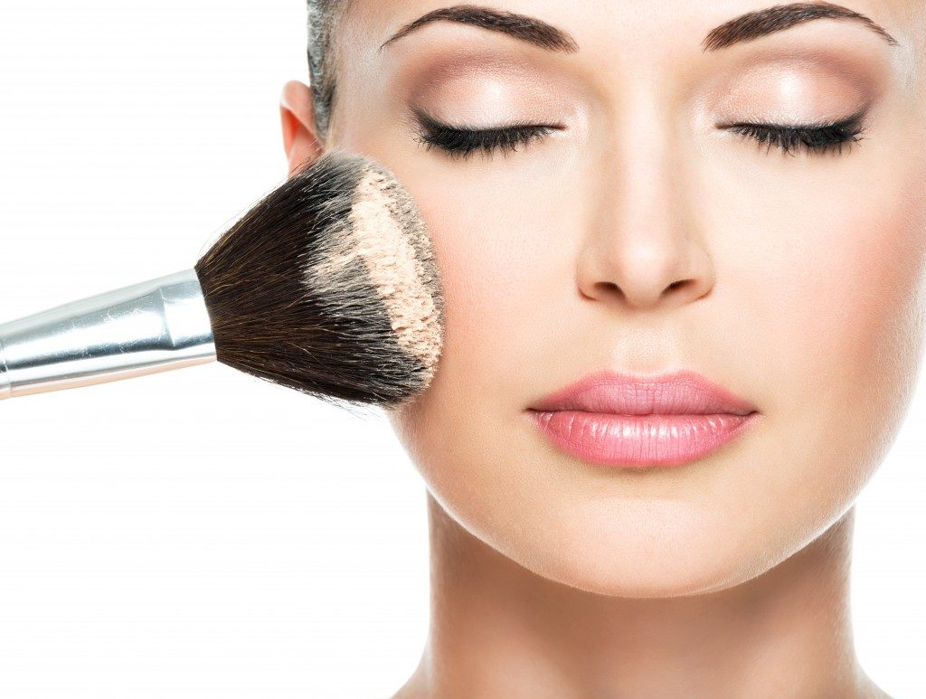 woman applying loose powder on face