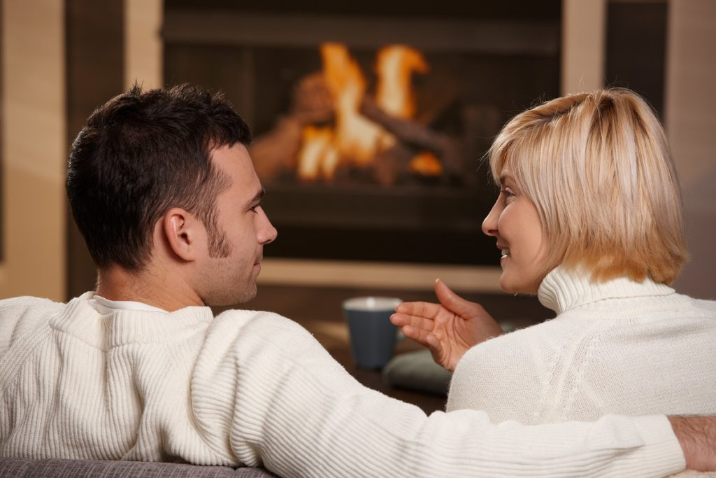 Couple talking in front of the fireplace
