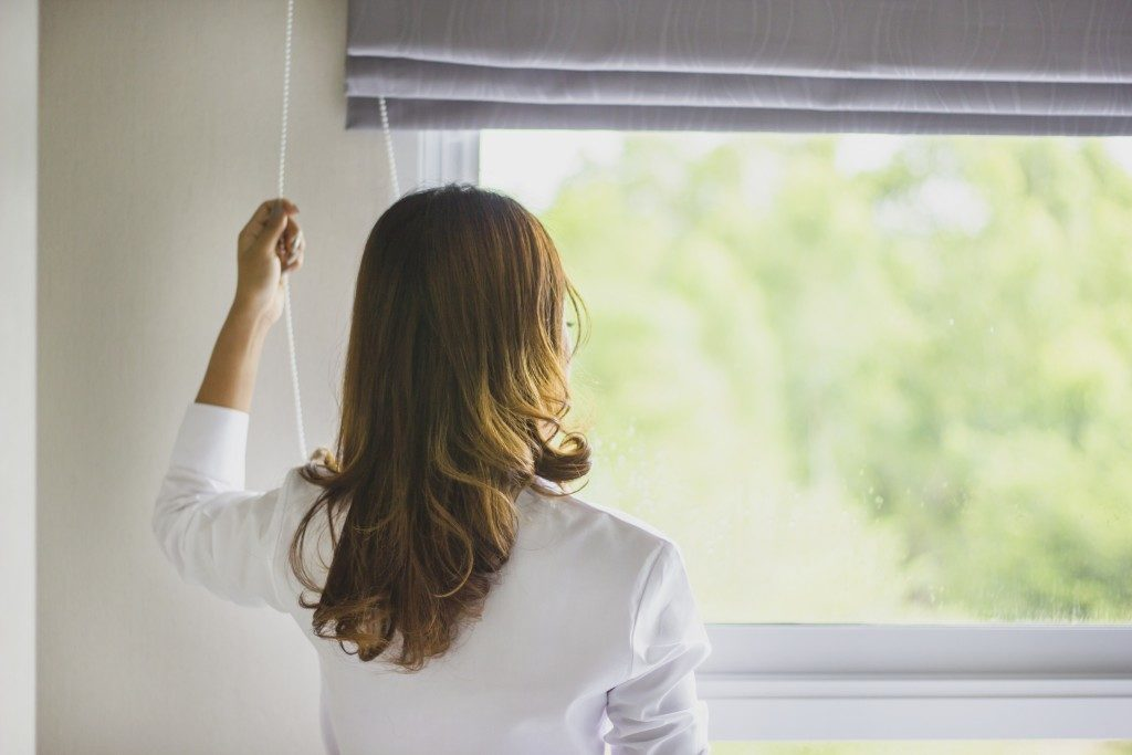 Woman pulling up the curtains to let in sunlight