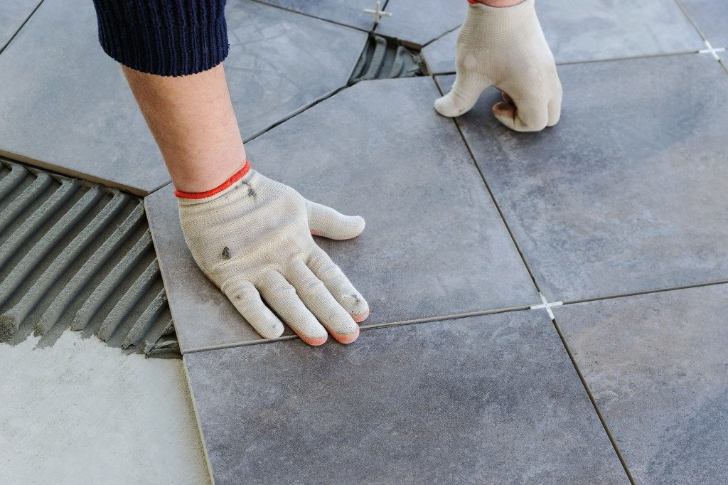 Man fixing the tiles on the floor