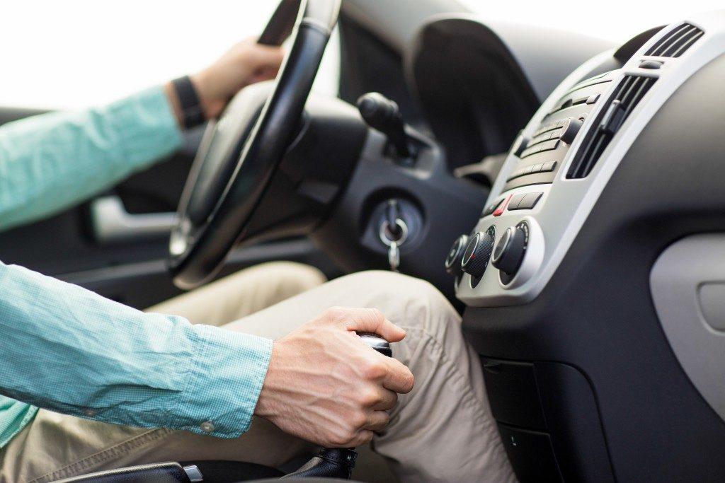 close up shot of hands of a man driving a car