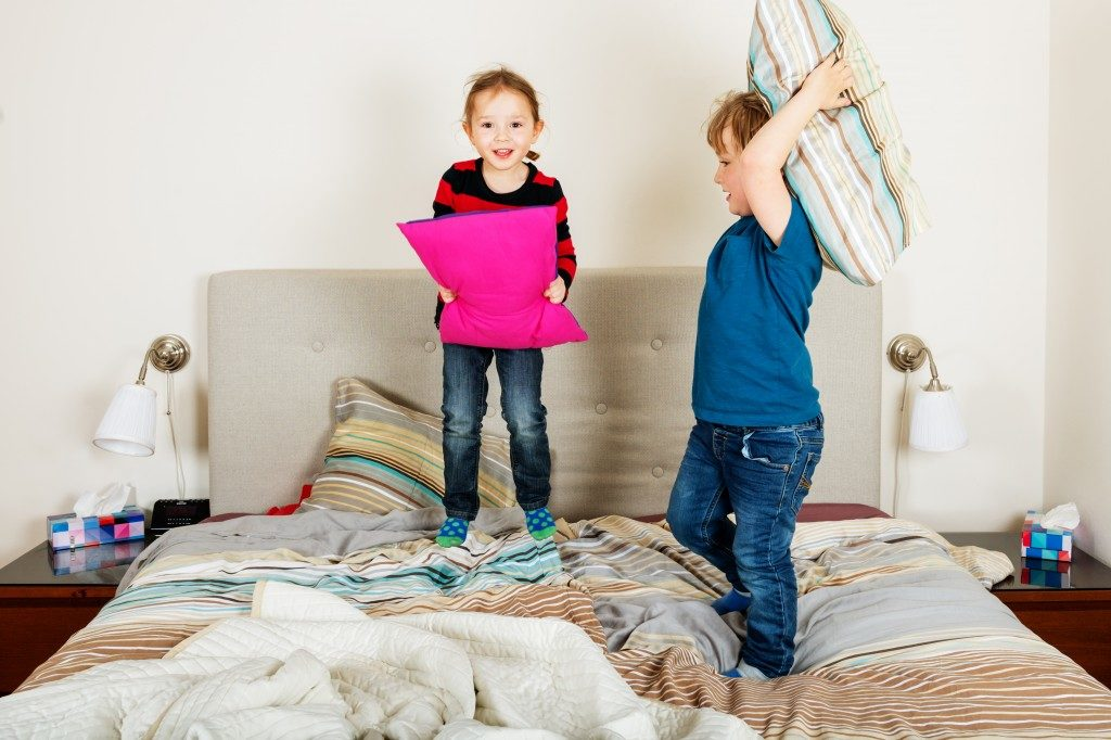 two kids having pillow fight on the bed