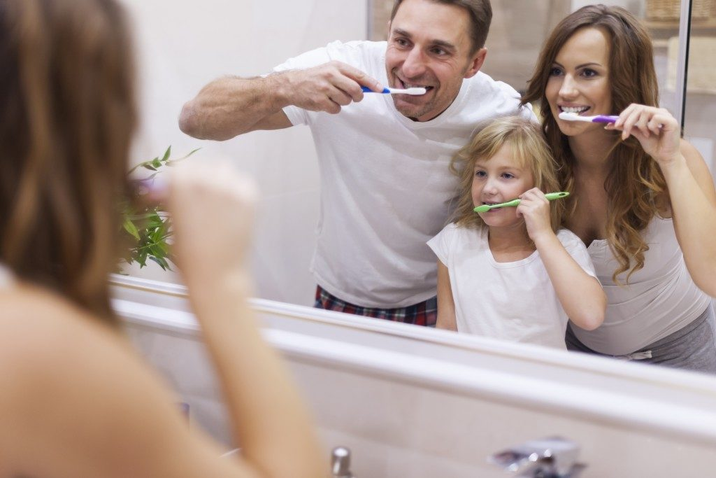 parents and child brushing their teeth