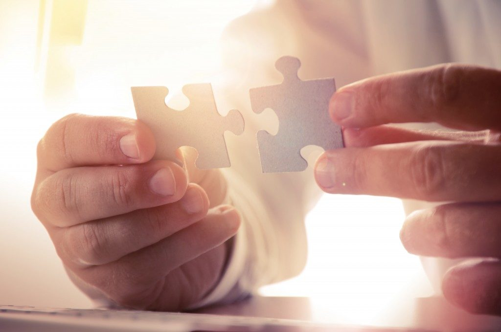 man linking puzzle pieces together