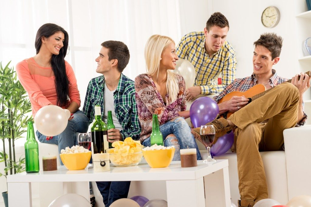 small group of young people hanging out at the house party