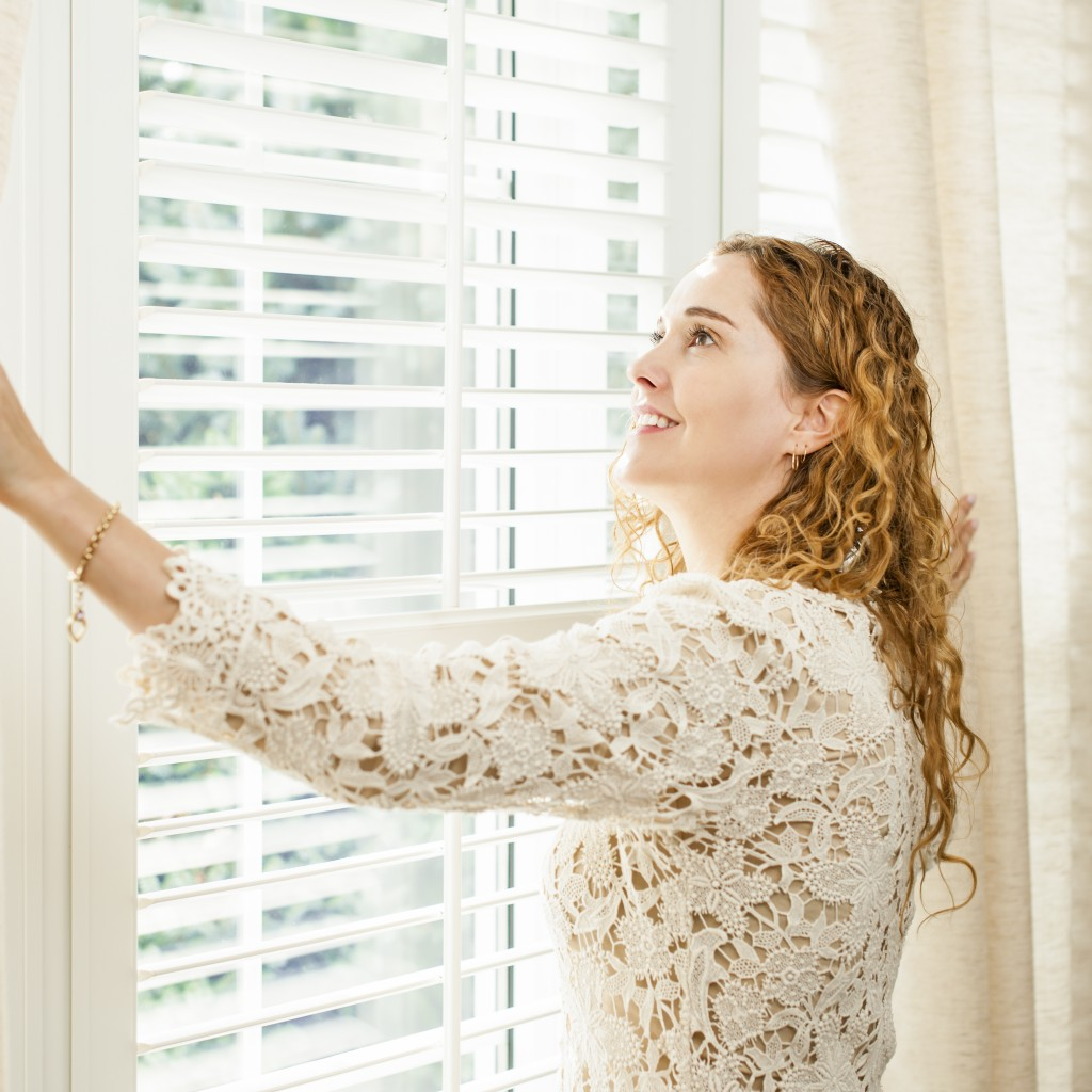 Happy woman looking out big bright window