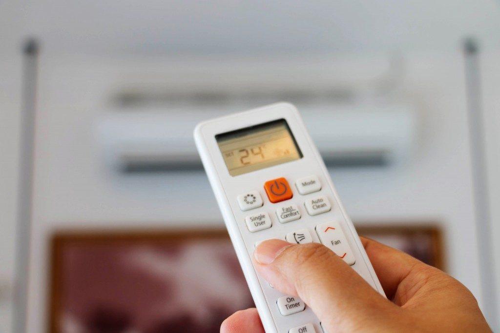person adjusting AC temperature
