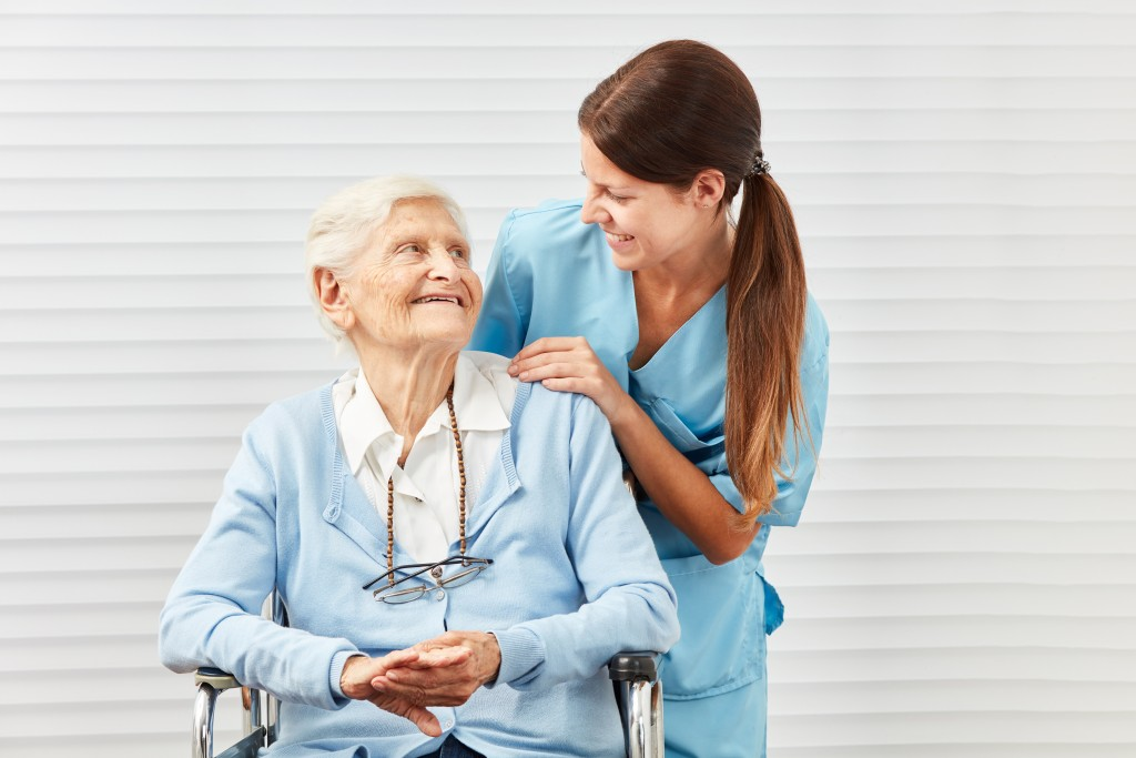 Nurse helping senior person on wheelchair