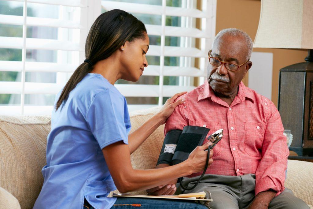 nurse checking blood pressure of senior