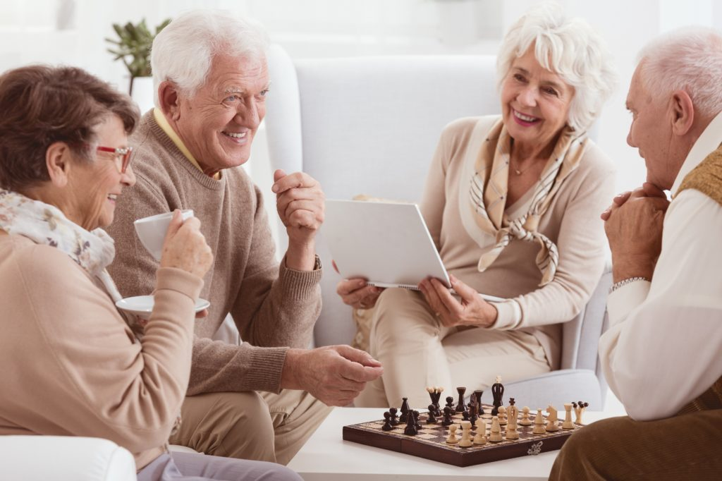 elderly people enjoying their time while playing and having a laptop