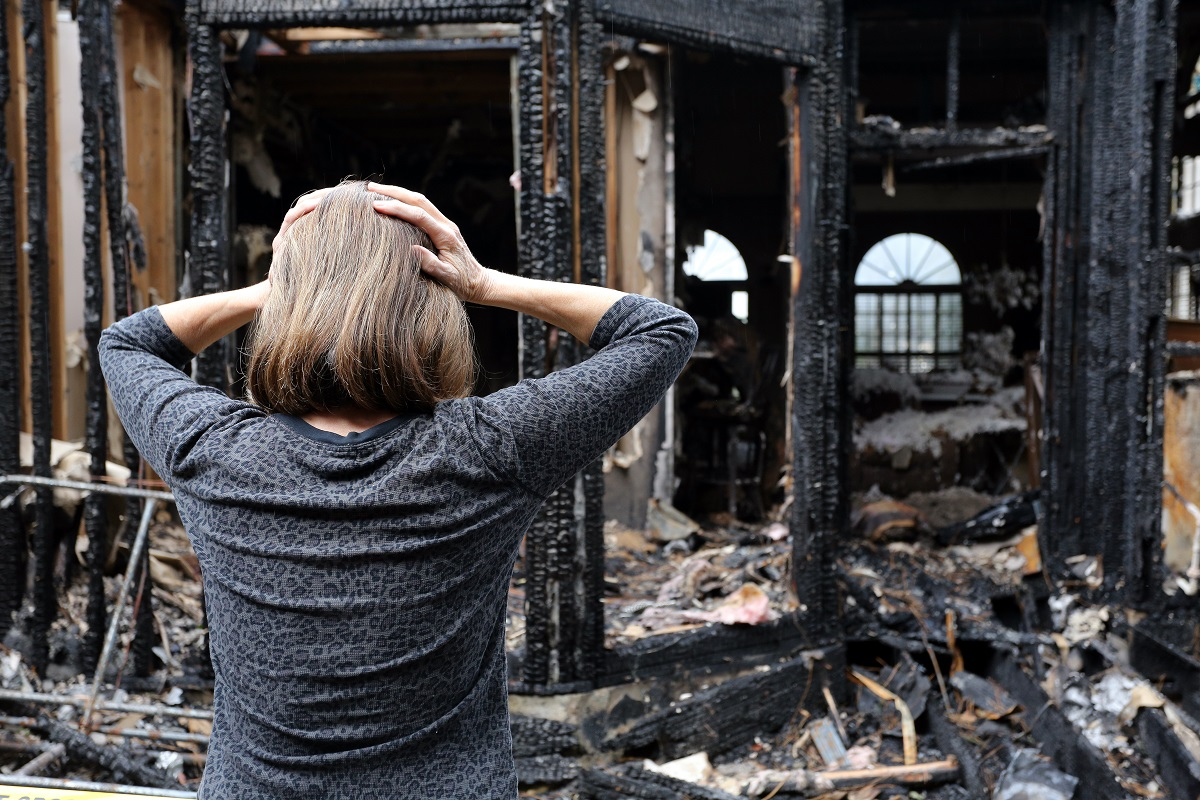 woman looking at her home damaged by the fire