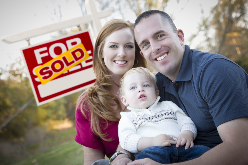 Family in Front of Sold Real Estate Sign