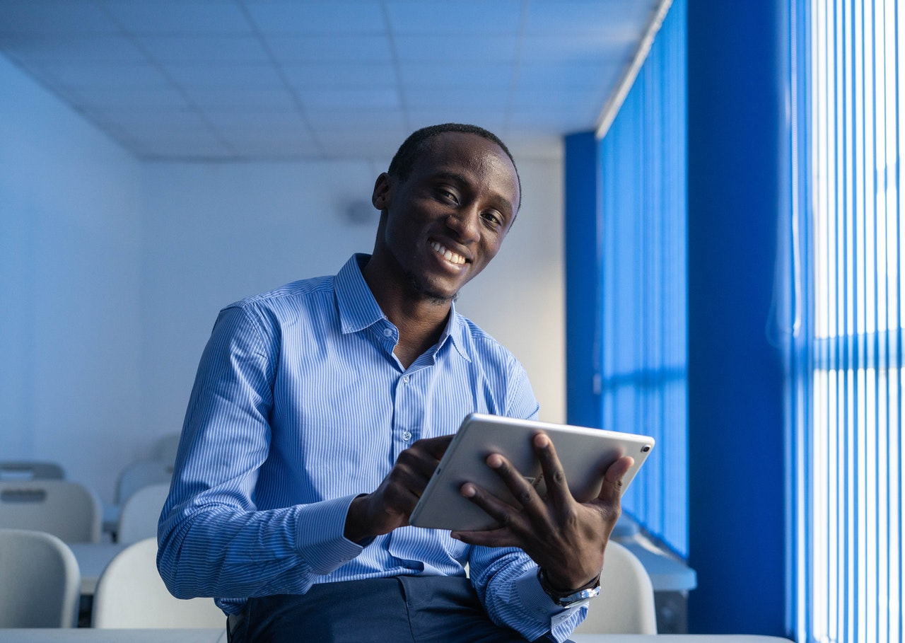 smiling man holding tablet