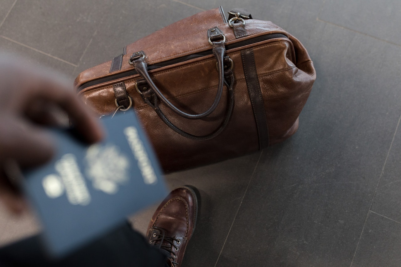 holding passport and luggage